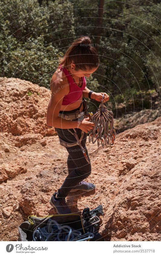 Sporty female alpinist preparing equipment for ascending woman cliff climb sport rock extreme nature climber adventure training athlete prepare activity