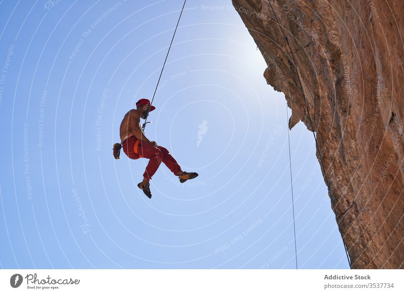 Strong male climber hanging on rope near rocky slope of mountain on sunny day man mountaineer strong sport secure equipment nature adventure activity cliff