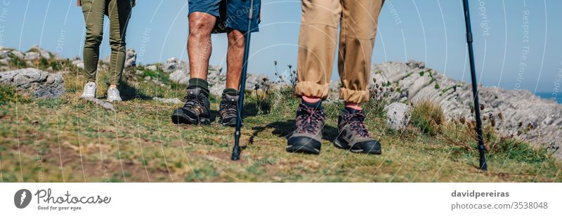 Three people practicing trekking outdoors unrecognizable group hikers mountain boots legs low section trekking sticks banner header web panorama panoramic woman