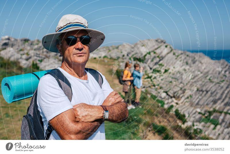 Senior man trekking looking at camera senior mature landscape hike nature countryside hikers summer mountain recreation hat serious sunglasses people hiking