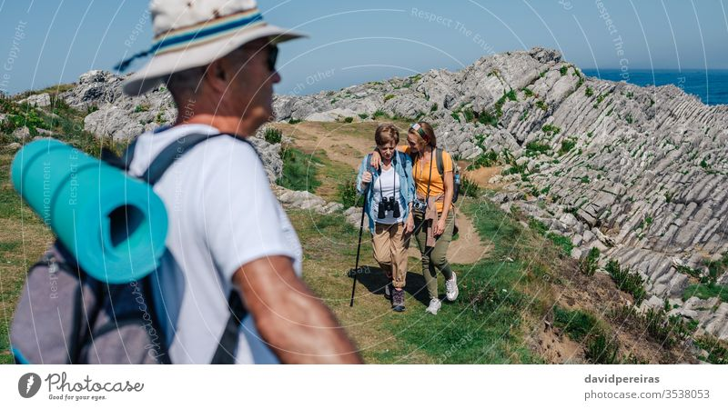 Family practicing trekking together outdoors hiking embracing senior mother daughter mountain field nature family summer recreation people activity backpack