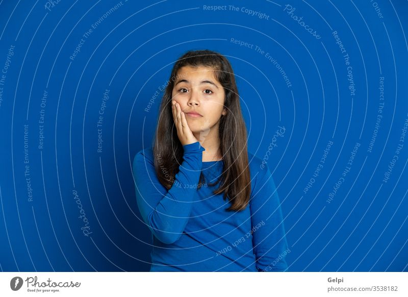 Adorable preteen girl with yellow jersey blue worried nervous thoughtful pensive think imagine imagination idea solution doubt doubtful female people person