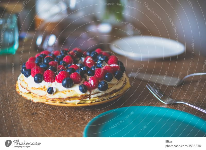 A cake or pie with raspberries and blueberries on a laid table piece of cake Cake eat cake Table Mint embellish Cream affectionately Delicious Berries Dessert