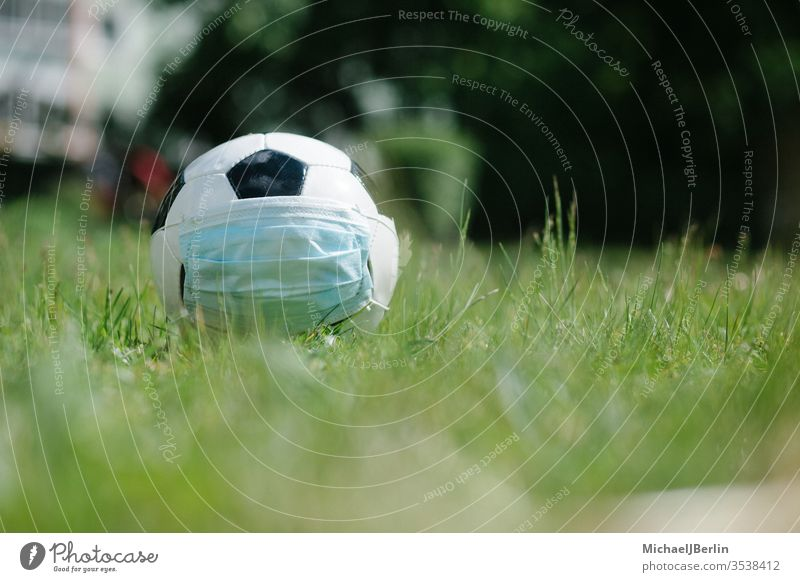 Soccer football with face mask for sports during covid-19 pandemic Football concept corona covid19 danger epidemic field game grass health hygiene natural