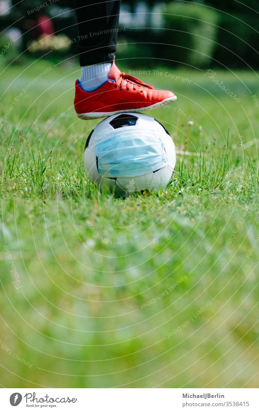 Foot and shoe with soccer football with face mask for sports during covid-19 pandemic Football Soccer concept corona covid19 danger epidemic feet field game