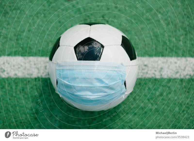 Soccer football with face mask for sports during covid-19 pandemic Football artificial concept corona covid19 danger epidemic field game grass green health