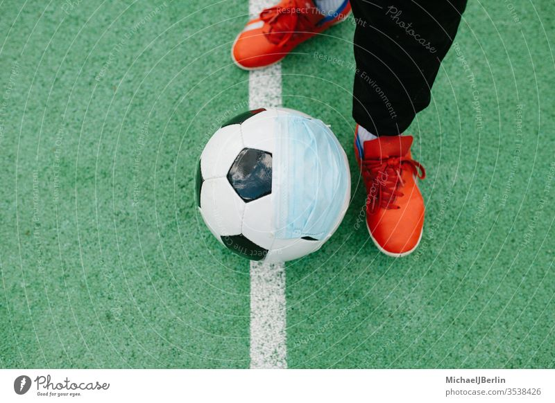 Kick off with soccer football with face mask for sports during covid-19 pandemic Foot Football Soccer artificial concept corona covid19 danger epidemic feet