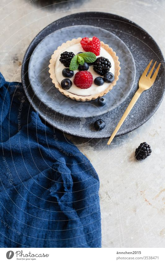 Berry tartlets on a dark blue plate with a golden fork Fork Plate Tartlet Nutrition Delicious Colour photo Interior shot Day Crockery Cutlery Deserted Appetite