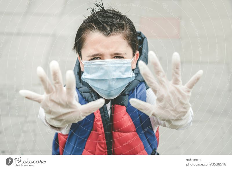 close-up of kid wearing medical mask spreading hands up coronavirus child epidemic pandemic quarantine covid-19 symptom medicine health childhood protection