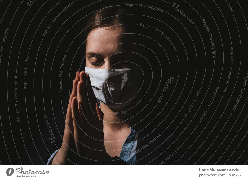 Religious woman with mask praying with hands for coronavirus covid-19 to end on black background adult caucasian christianity corona italy corona virus