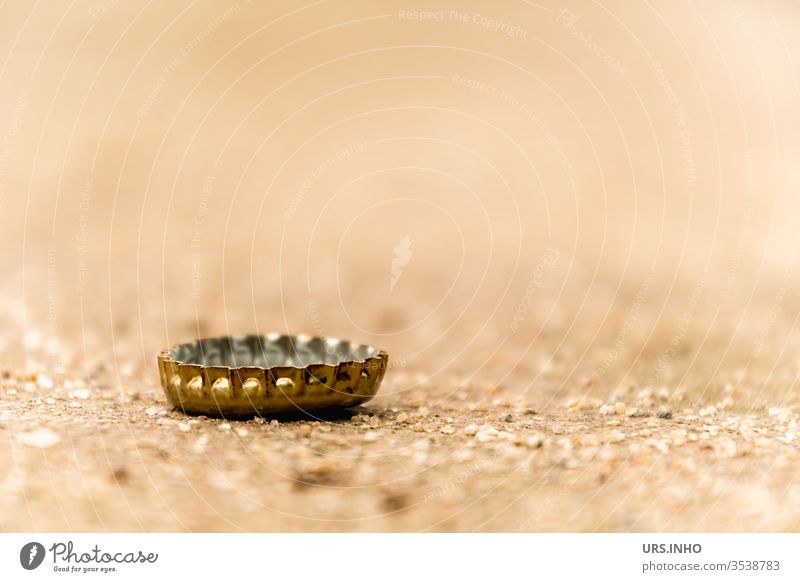 A crown cork on sandy soil rarely remains alone Crown cork beer closure Ground jettisoned Lie Gold Beige Bottle lid close up Close-up Deserted Sheet metal piece
