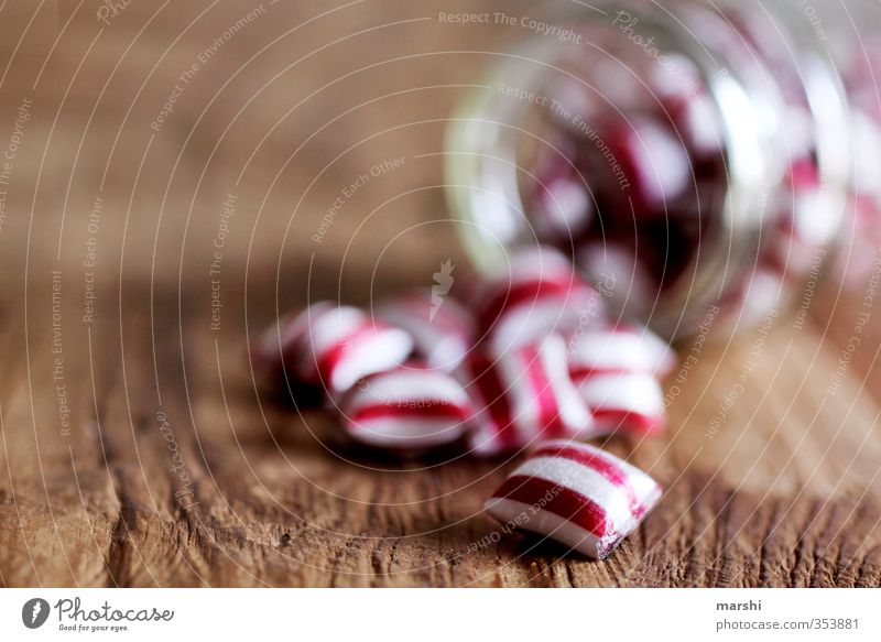 striped candy Food Nutrition Eating Red White Candy Shallow depth of field Glass Wooden table Delicious Calorie Lick Stripe Striped Tasty Sense of taste