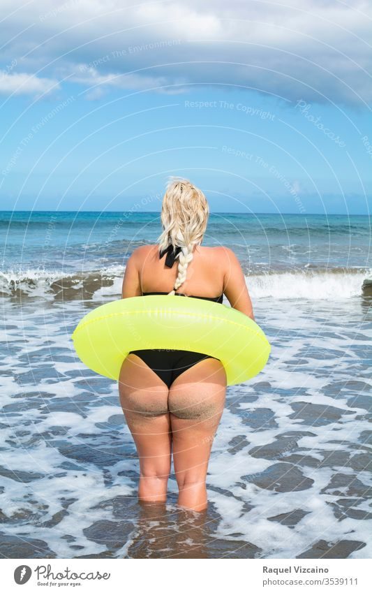 Blonde woman on her back in a bikini, with a float around her waist, entering the sea. beach summer young beautiful ocean beauty water sand body vacation