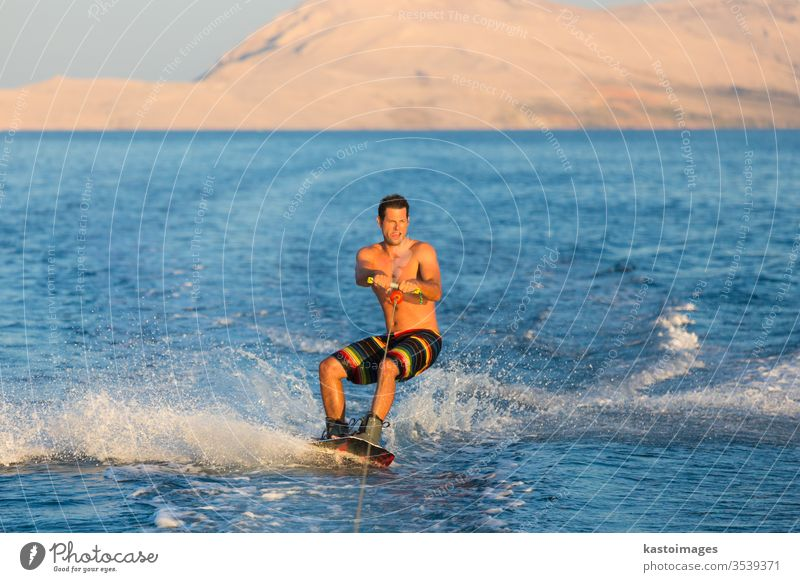 Wakeboarder in sunset. wakeboard sport man extreme wakeboarding sea wave cable fun water recreation splash young male action summer person outdoor wakeboarder