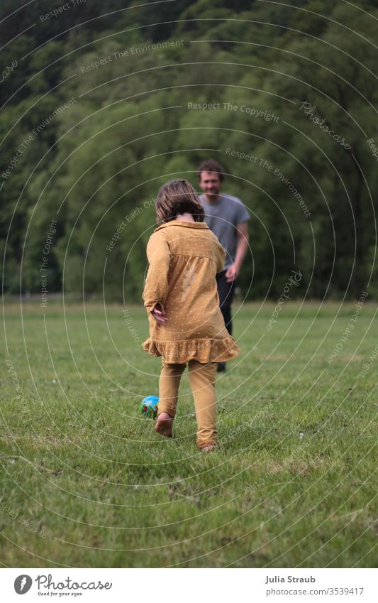 Child playing football with a man in a meadow Father girl soccer Meadow Places huts Forest Edge of the forest Dress Ball mustard yellow Playing Running move