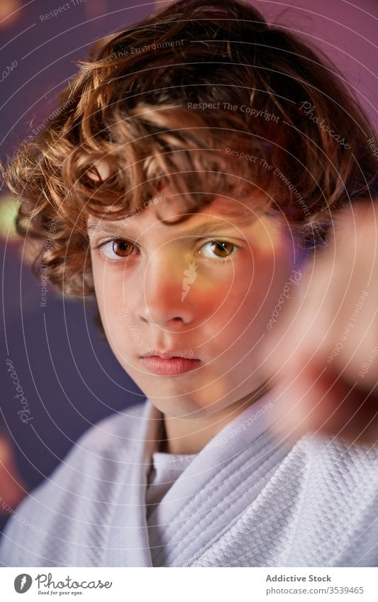 Angry young boy in kimono practicing judo in light room angry kick fighter martial determine attack punch practice fist training sport illuminate concentrate