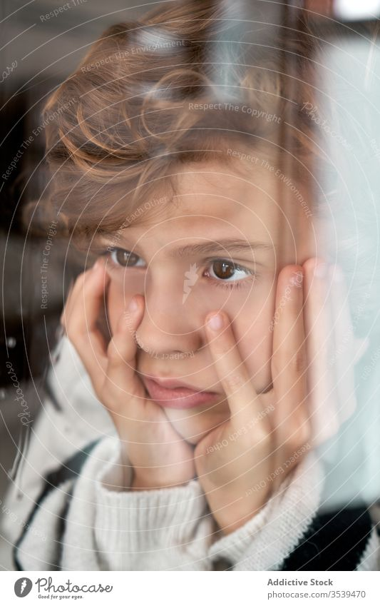 Bored boy looking out wet window bored rain hand on cheek rest home cozy weather child kid sad childhood tranquil lifestyle lonely adorable calm unhappy