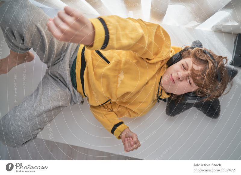 Satisfied child in headphones lying on table and enjoying music in light modern room boy chill listen home happy song music lover relax playlist lounge carefree