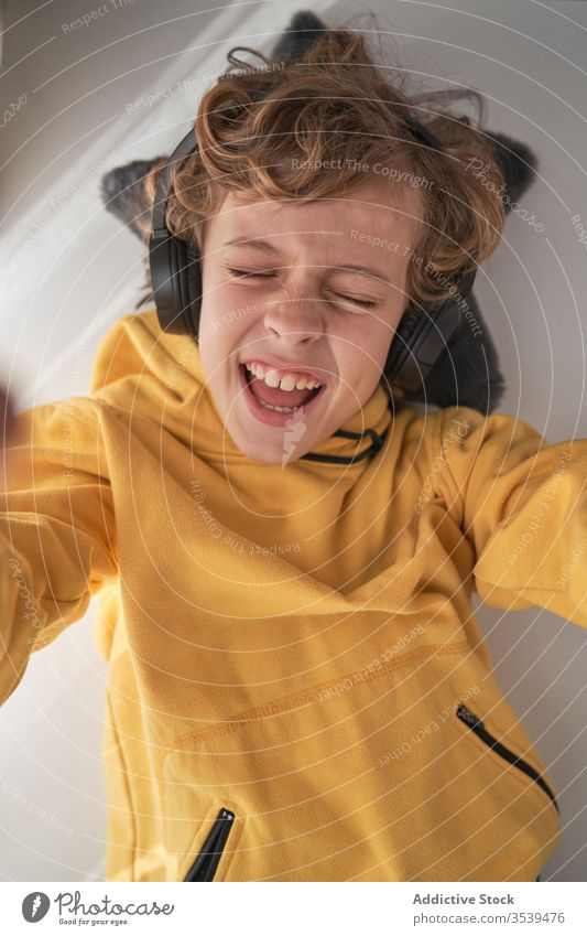 Satisfied child in headphones lying on table and enjoying music in light modern room boy chill listen home happy song music lover relax playlist lounge audio