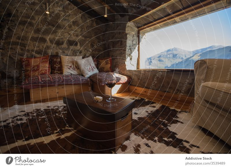 Interior of old stone house in Cantabria with cozy sofa near wide window interior country mountain comfort wine leisure lounge table apartment style furniture