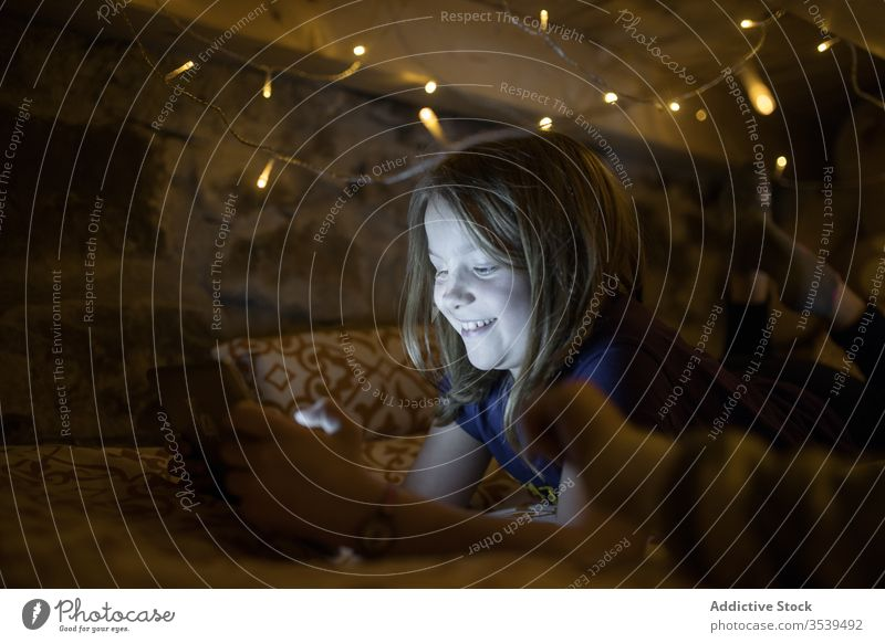 Content girl using tablet while resting on bed decorated with garland browsing night cozy calm glow illuminate comfort lounge home internet relax leisure spain