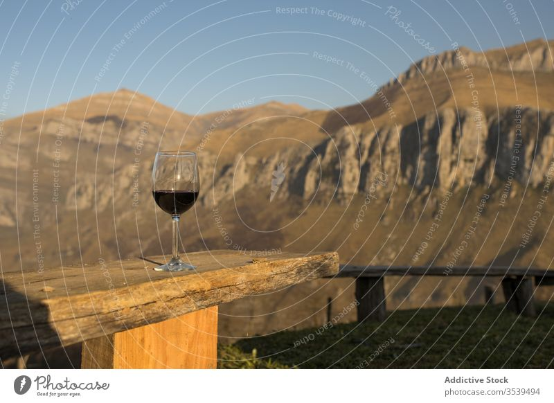 Glass of red wine on wooden railing against countryside mountains nature meadow sunset view idyllic glass beverage alcohol relax landscape peaceful travel