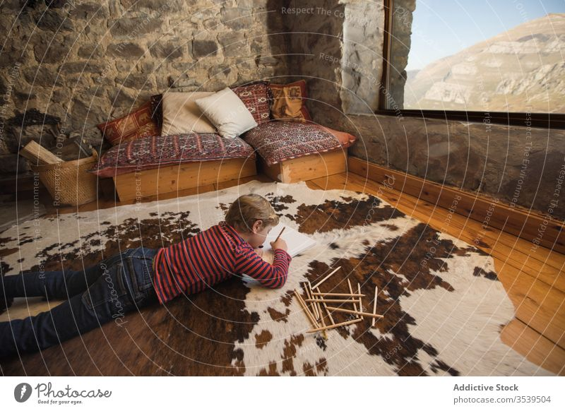 Kid drawing with colored pencils in sketchbook in living room boy house country cabin inspiration nature young carpet spain cantabria stone creative leisure