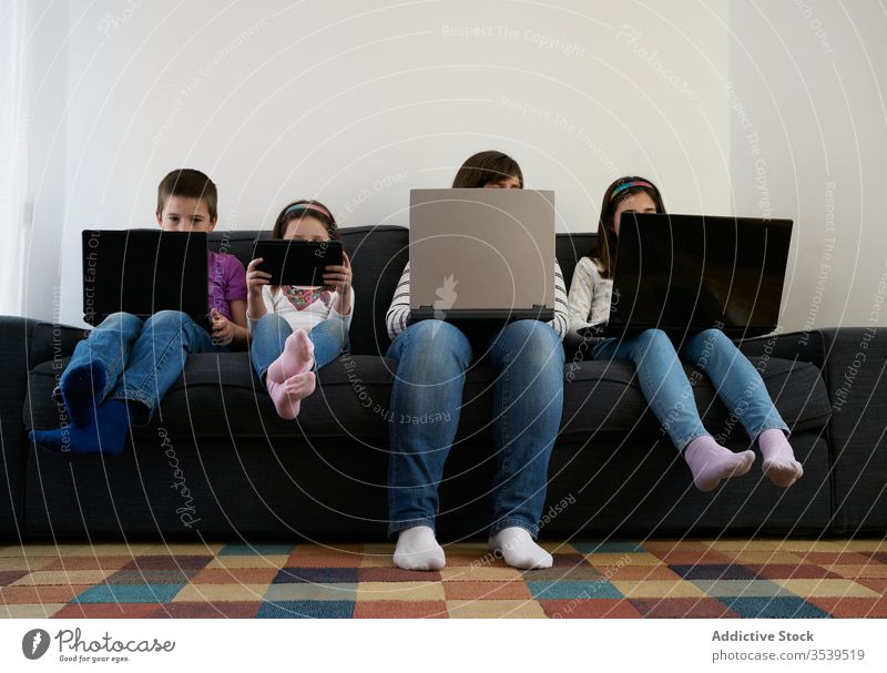 Serious mother and kids spending time together using gadgets on sofa at home children laptop busy addict browsing woman leisure separate sibling parent internet