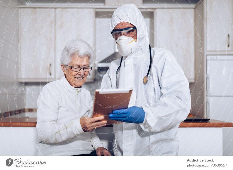 Medical specialist explaining prescription to senior patient during quarantine coronavirus tablet home doctor care medical practitioner health care visit help