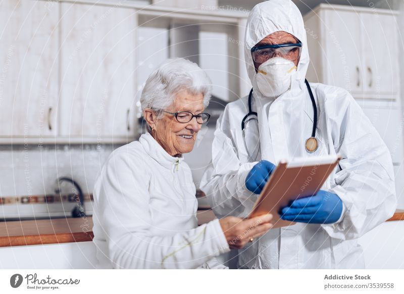 Medical specialist explaining prescription to senior patient during quarantine coronavirus tablet home doctor care medical browsing practitioner health care