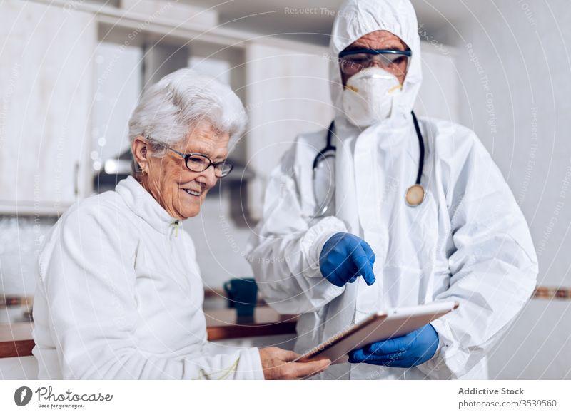 Doctor explaining medical information to senior patient at home during coronavirus quarantine doctor care tablet show point prescription practitioner