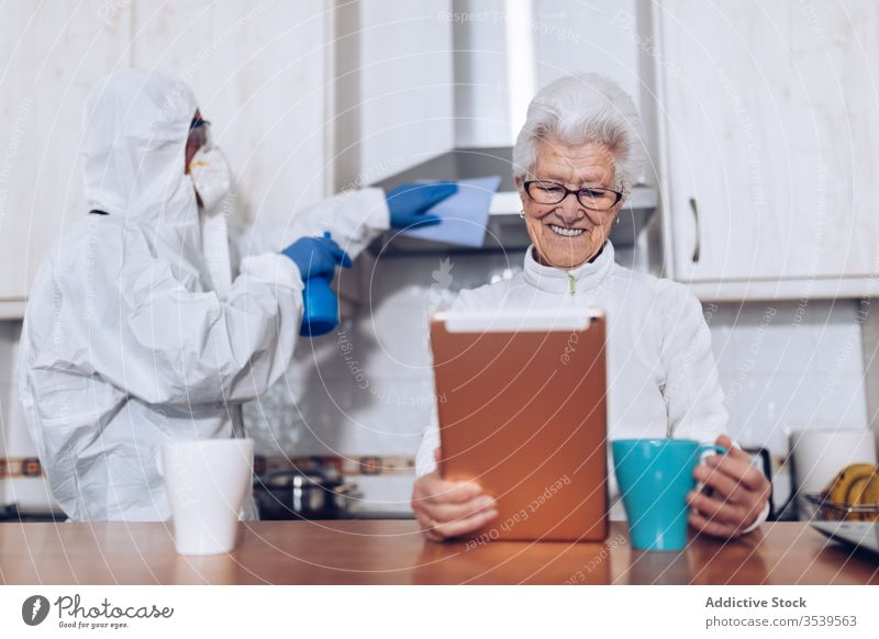 Home care employee helping senior client at home during quarantine coronavirus assistant visit show support kitchen cheerful happy book service social flu