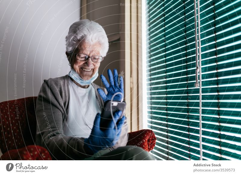 Cheerful senior woman chatting on smartphone during self isolation at home stay coronavirus window using cheerful communicate mobile device gadget smile