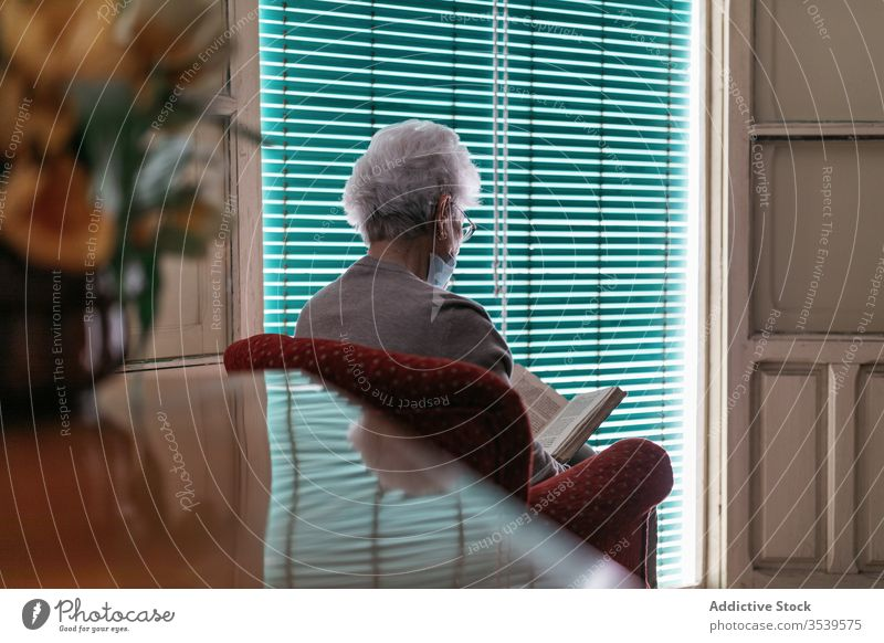 Senior lady in protective mask and gloves reading book at home stay coronavirus woman senior window lonely quarantine prevent old female alone solitude aged