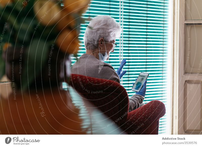 Old woman having video conversation on smartphone at home stay coronavirus senior video call using cheerful communicate gesture greeting mobile device gadget
