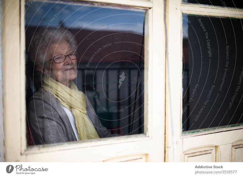 Senior woman looking out window senior coronavirus home lonely anxious desperate unhappy sad quarantine prevent old female protect alone depression stress tired