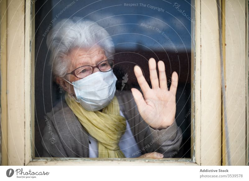 Senior woman in protective mask looking out window senior coronavirus home lonely anxious desperate unhappy sad quarantine prevent old female alone depression