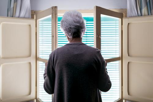 Gray haired woman standing in front of window at home senior lonely quarantine coronavirus shutter open alone old female solitude concept aged safety isolation