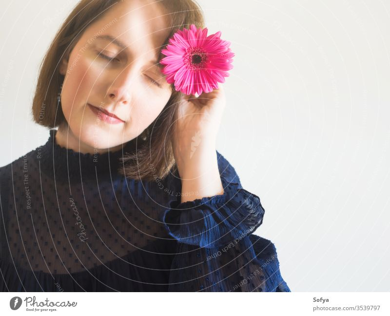 Beautiful female portrait with pink gerbera flower woman beauty mothers day fashion one unique skin eyes care face young hand holding spring springtime romantic