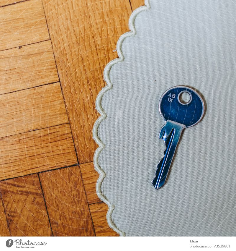 A blue key on a cloth cover on wood Key Blanket Blue dwell House key Safety Interior shot Day at home Flat (apartment)