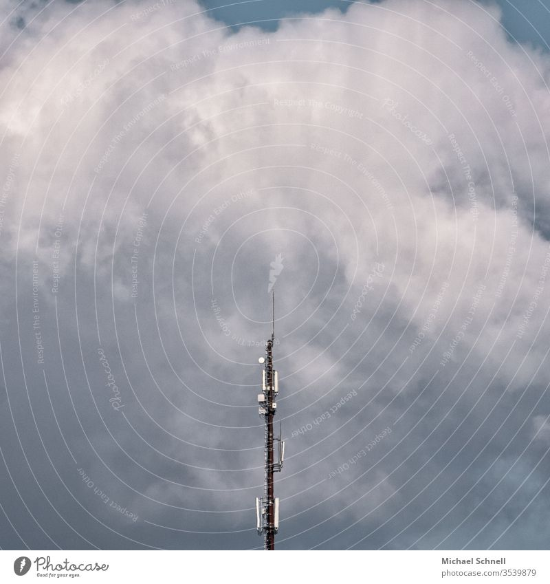 Transmitter mast in front of mighty clouds Broacaster Broadcasting tower Sky Blue Antenna Clouds Technology Telecommunications Deserted Colour photo Communicate