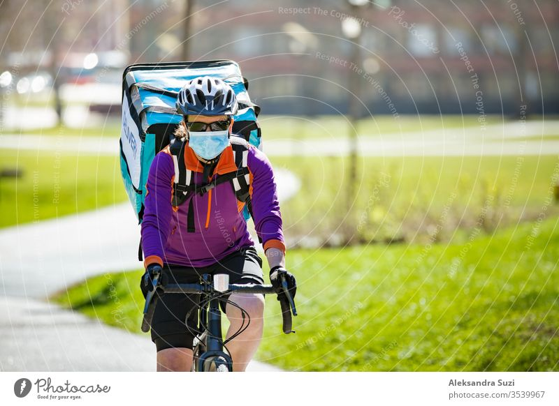 Woman in helmet and protective mask with big food delivery backpack riding bike on the street. Sunny spring day in the city. Portrait of a female courier in a medical mask.