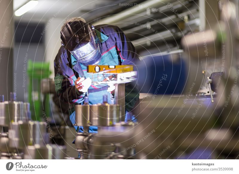 Industrial worker welding in metal factory. welder industry inox steel craftsman industrial manufacturing engineering skill mask safety spark protection flash
