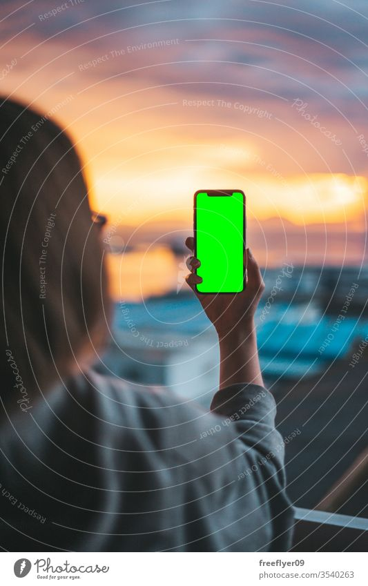 Woman holding a smartphone on a green screen photo photography photographing taking photographs picture hand technology shot using mobile mobile phone device