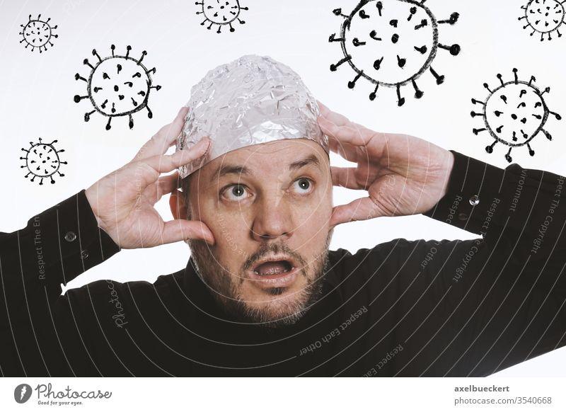 paranoid man wearing tin foil hat against corona virus covid-19 conspiracy theory coronavirus paranoia fear pandemic sars-cov-2 comic 5G aluminum tinfoil