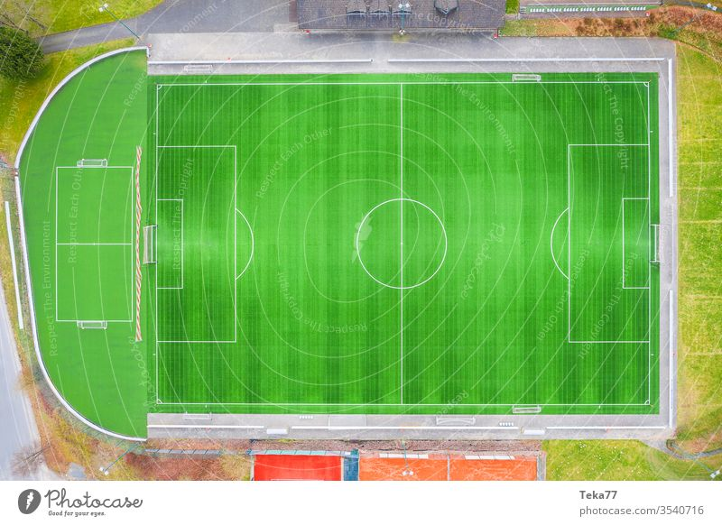 a green empty soccer field from above soccer field goal soccer goal lines sport sport place small soccer field grass sun shadow sports running track ash field