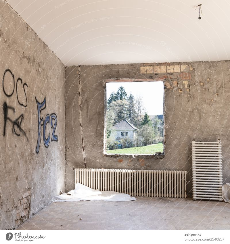 Room without furniture and without wall cladding, brickwork peeps out through plaster, two radiators leaning against the wall, graffiti on the walls, through frameless window opening views of meadow and next villa-like house