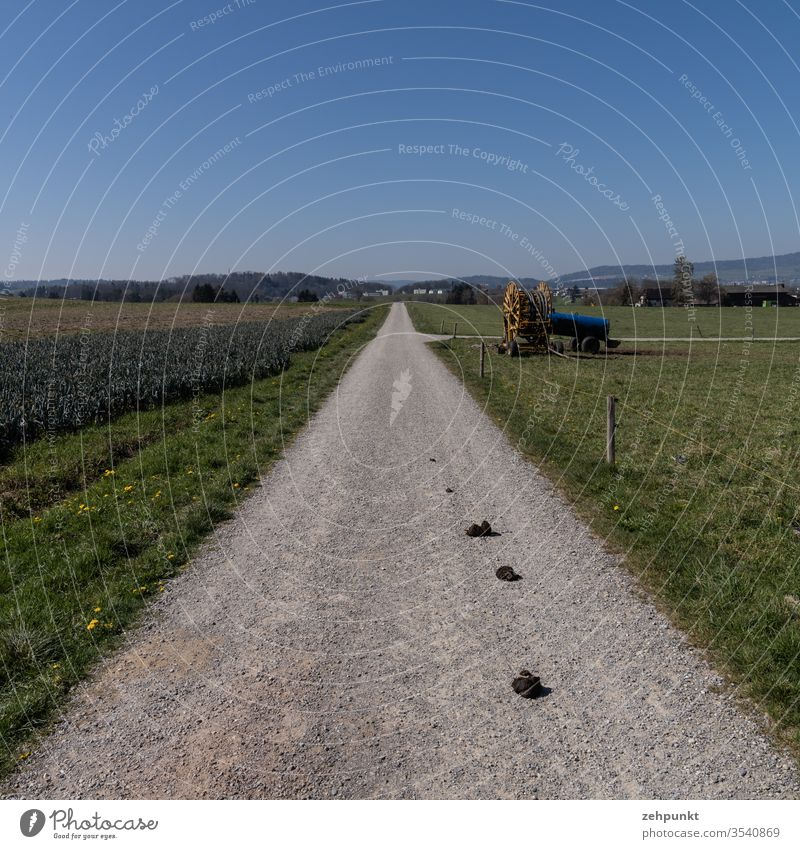 View along a path over farmland, agricultural machinery at the next crossroads, in the background a settlement Agriculture off the beaten track