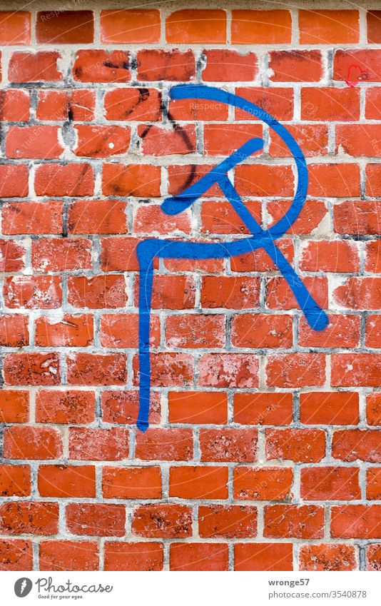 Hammer and sickle - a political symbol sprayed with blue paint on red brick hammer and sickle Symbols and metaphors Communism Politics and state Might Russia