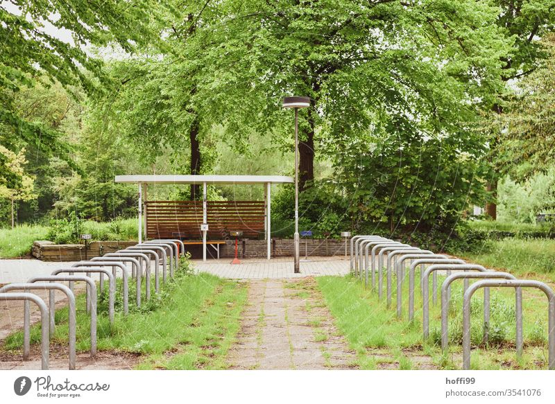 "empty bicycle racks in the courtyard surrounded by lush green Bicycle rack ""Bicycle stand bicycle holder Bicycle lot wheel stand Parking lot parking space"